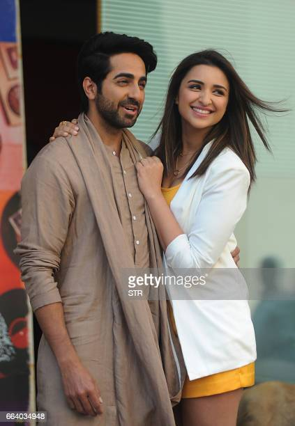Indian Bollywood actors Ayushmann Khurrana and Parineeti Chopra pose for a photograph during a promotional event for the forthcoming Hindi film 'Meri...