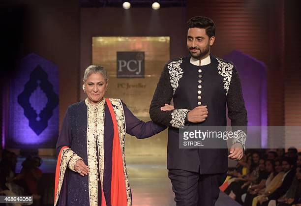 Indian Bollywood actors Jaya Bachchan and her son Abhishek Bachchan model creations by designer Manish Malhotra during a charity fashion show in...