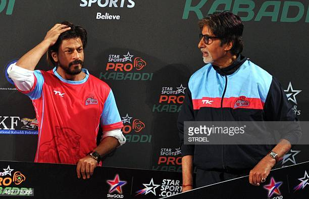 Indian Bollywood actors Shah Rukh Khan and Amitabh Bachchan talk during a professional kabaddi league match in Mumbai on late July 26 2014 AFP...