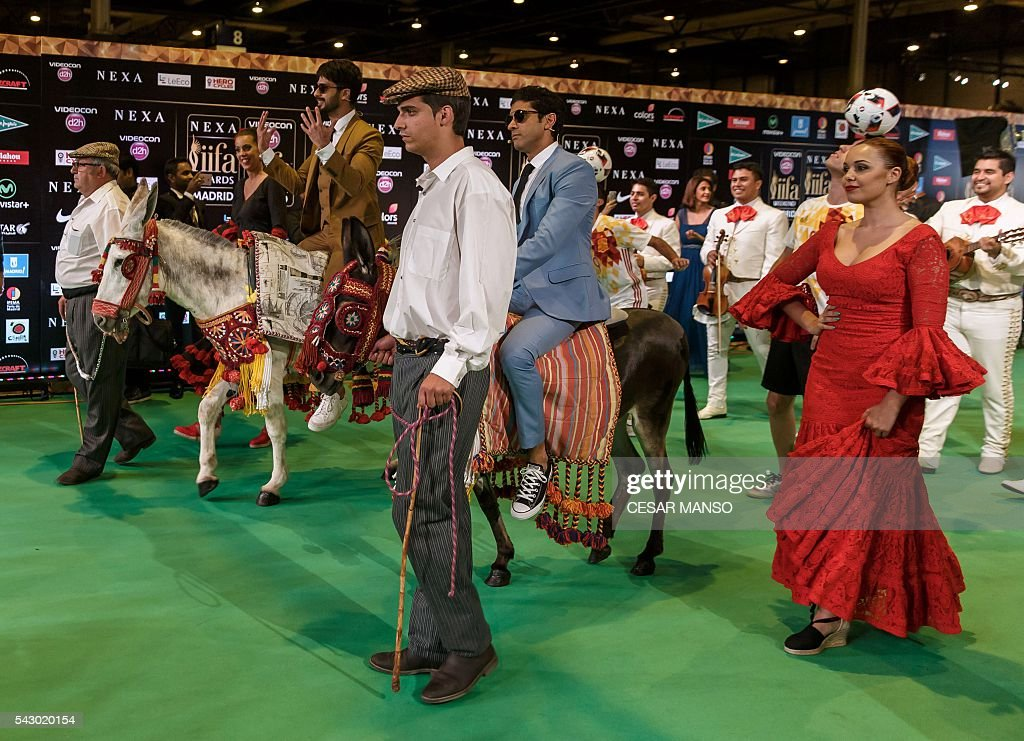 Indian Bollywood actors Shahid Kapoor (2ndL) and Farman Akhtar (C) arrive on donkeys to pose on the green carpet few moments before the 17th edition of IIFA Awards (International Indian Film Academy Awards) in Madrid on June 25, 2016. The IIFA Awards are presented annually by the International Indian Film Academy to honour both artistic and technical excellence of professionals in Bollywood, the Hindi language film industry. / AFP / CESAR