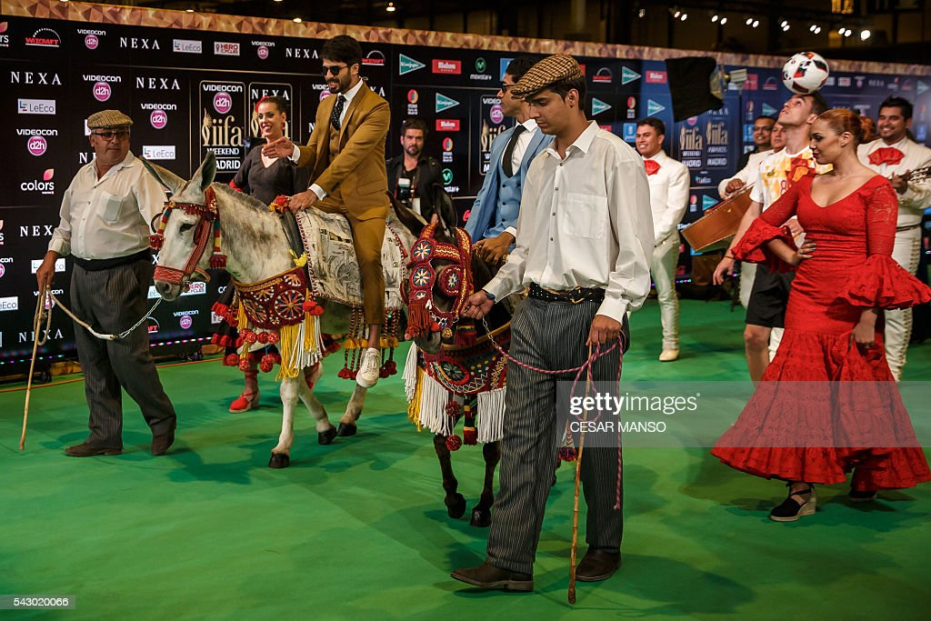 Indian Bollywood actors Shahid Kapoor (L) and Farman Akhtar (C) arrives on donkeys to pose on the green carpet few moments before the 17th edition of IIFA Awards (International Indian Film Academy Awards) in Madrid on June 25, 2016. The IIFA Awards are presented annually by the International Indian Film Academy to honour both artistic and technical excellence of professionals in Bollywood, the Hindi language film industry. / AFP / CESAR