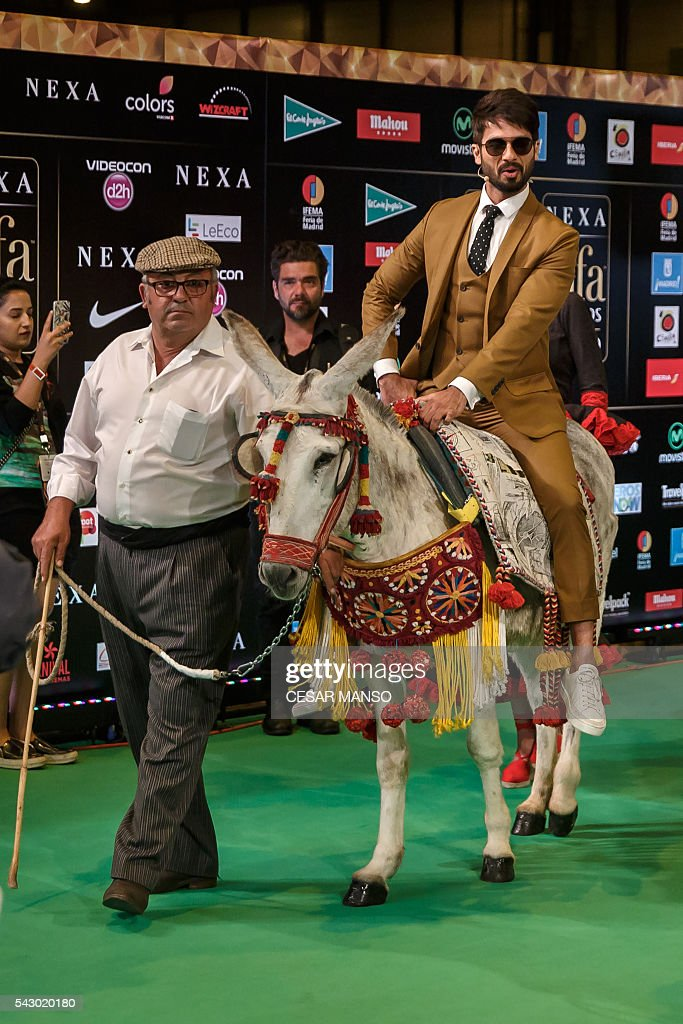 Indian Bollywood actors Shahid Kapoor (R) arrives on a donkey to pose on the green carpet few moments before the 17th edition of IIFA Awards (International Indian Film Academy Awards) in Madrid on June 25, 2016. The IIFA Awards are presented annually by the International Indian Film Academy to honour both artistic and technical excellence of professionals in Bollywood, the Hindi language film industry. / AFP / CESAR