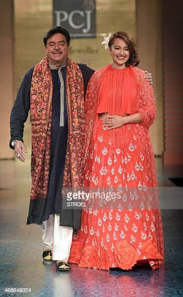 Indian Bollywood actors Shatrughan Sinha and his daughter Sonakshi Sinha model creations by designer Manish Malhotra during a charity fashion show in...