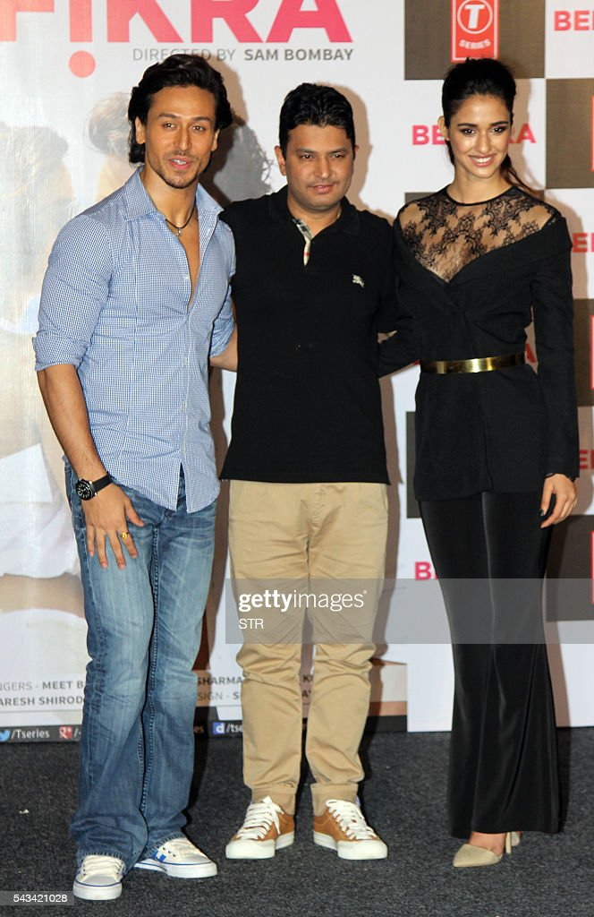Indian Bollywood actors, Tiger Shroff (L) and Disha Patani (R) pose with producer Bhushan Kumar during the launch of the single Hindi album 'Befikra' in Mumbai on June 28, 2016. / AFP / STR