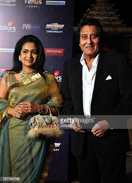 Indian Bollywood actors Vinod Khanna poses with his wife as they arrive for the '7th Apsara Awards' ceremony in Mumbai on January 25 2012 AFP...