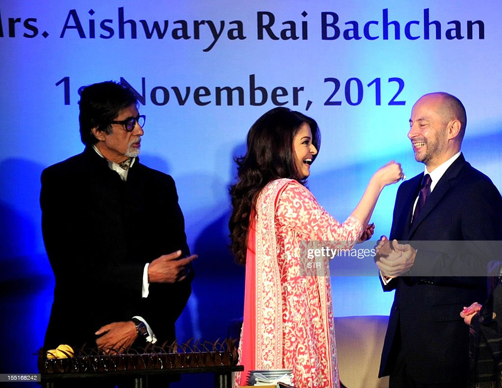 Indian Bollywood actress Aishwarya Rai Bachchan (C) gestures to French ambassador to India, Francois Richier (R), after she was conferred with the French civilian award, Officer Dan Ordre Arts et des Lettres as her father in-law Indian Bollywood Actor Amitabh Bachchan looks on in Mumbai on November 1, 2012.