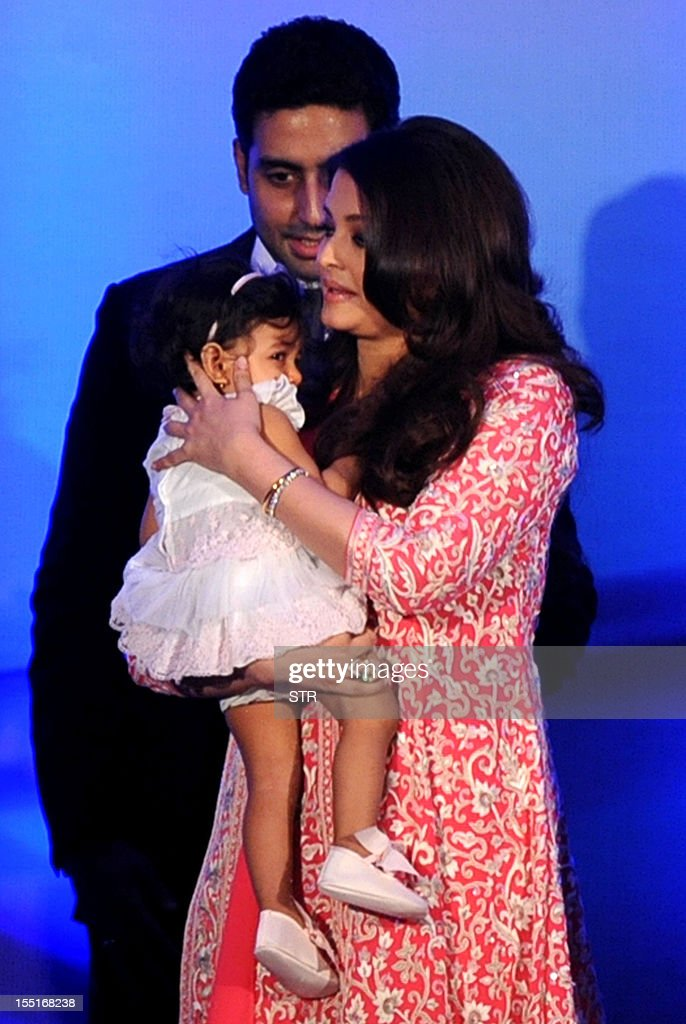 Indian Bollywood actress Aishwarya Rai Bachchan holds her daughter Aradhya as her husband Abhishek Bachchan looks on after Aishwarya was conferred with the French civilian award, Officer Dan Ordre Arts et des Lettres in Mumbai on November 1, 2012. AFP PHOTO/STR