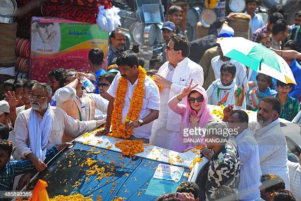 Indian Bollywood actress Amisha Patel gestures from the open sunroof of a car during an election roadshow for Congress candidate for Allahabad...