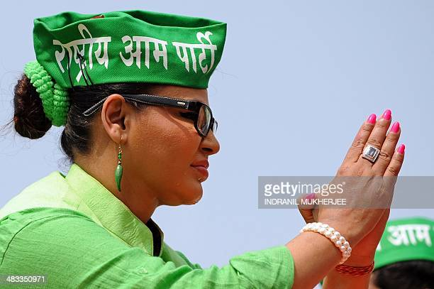Indian Bollywood actress and Rashtriya Aam Party candidate Rakhi Sawant flaunts earrings in the shape of green chillies her party's election symbol...