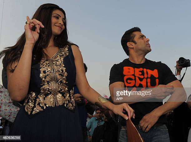 Indian Bollywood actress Daisy Shah gestures while Bollywood actor Salman Khan flies a kite during a promotional event for the film 'Jai Ho' at a...