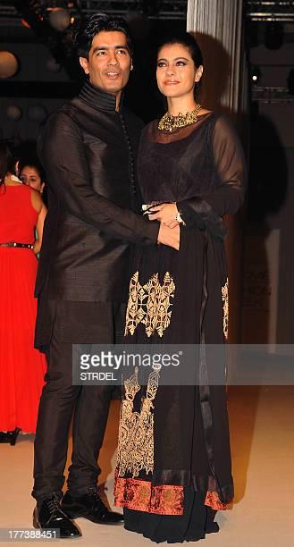 Indian Bollywood actress Kajol Devgan poses with designer Manish Malhotra during the Lakme Fashion Week Winter/Festival 2013 in Mumbai on August 22...
