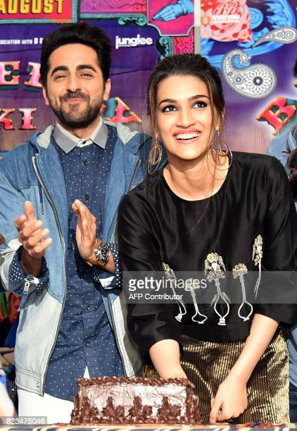 Indian Bollywood actress Kriti Sanon smiles next to actor Ayushmann Khurrana while cutting her birthday cake during the promotion of her upcoming...