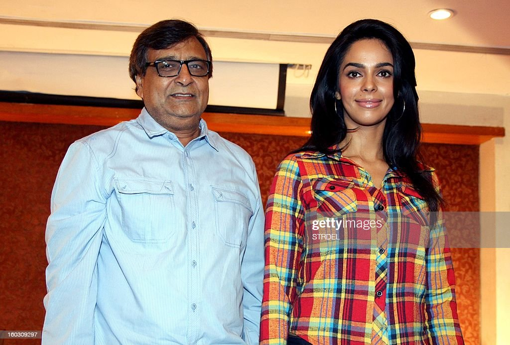 Indian Bollywood actress Mallika Sherawat (R) poses for a photo during a promotion for the upcoming Hindi film Dirty Politics, directed by K.C. Bokadia (L) in Mumbai on January 28, 2013. AFP PHOTO/ STR