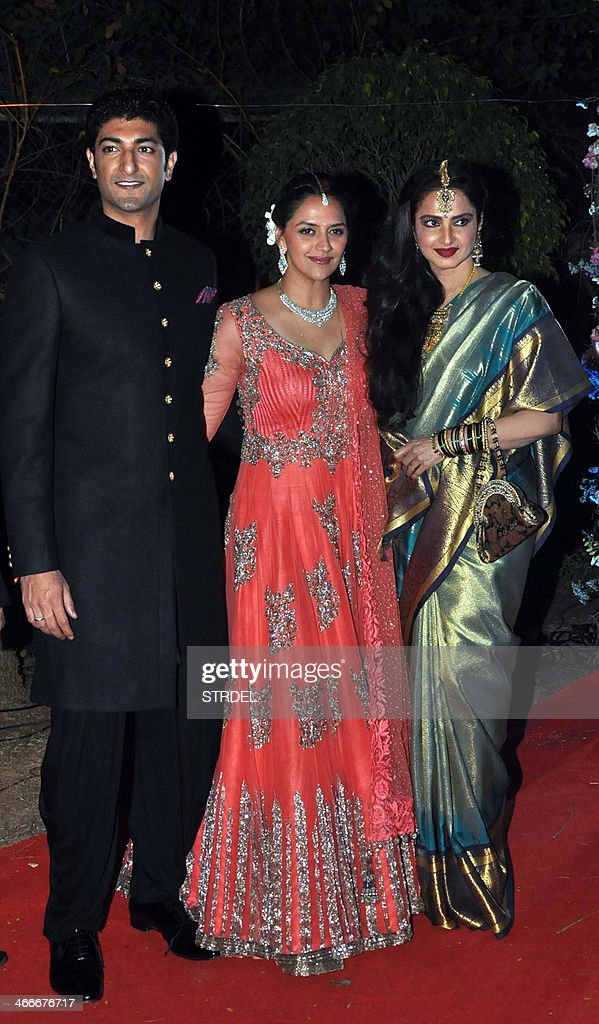 Indian Bollywood actress Rekha (R) poses as she attends the wedding reception of actress Ahana Deol (C) and husband Vaibhav Vohra (L) in Mumbai on February 2, 2014.