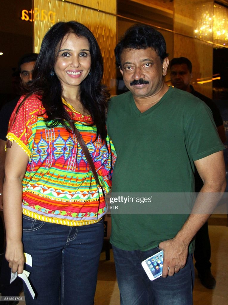 Indian Bollywood actress Suchitra Krishnamoorthi (L) and director Ram Gopal Varma pose for a photograph during a promotional event for the forthcoming Hindi film 'Veerappan' in Mumbai on late May 26, 2016. / AFP / STR