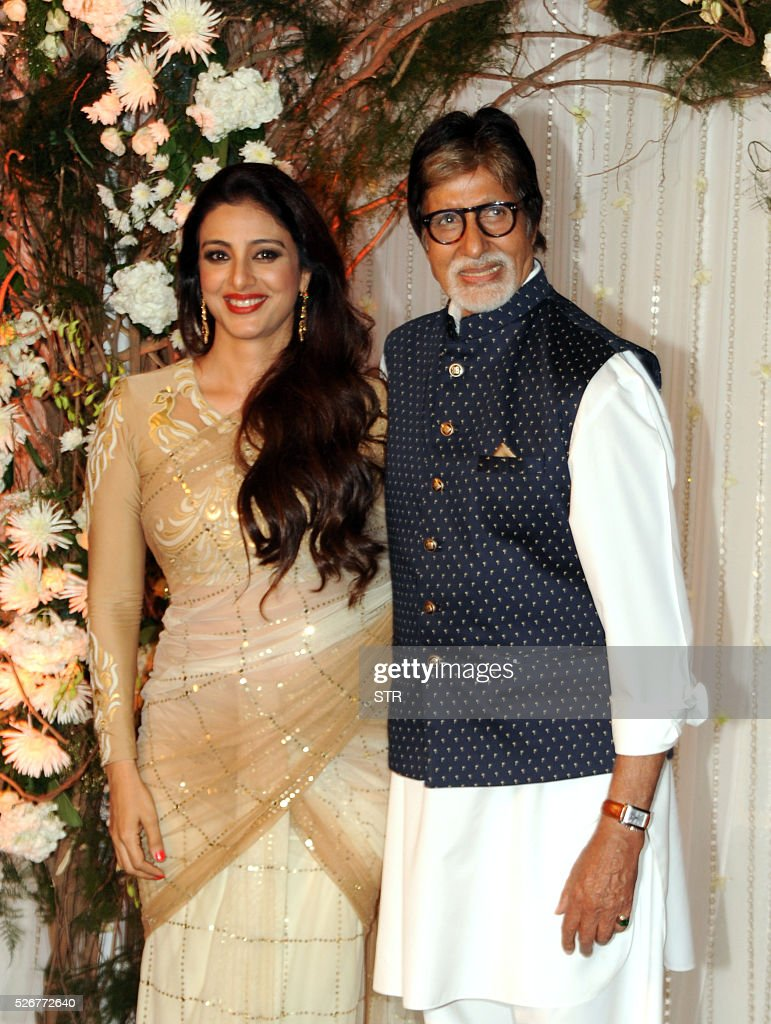 Indian Bollywood actress Tabu(L) and actor Amitabh Bachchan pose as they attend a reception after the wedding of fellow thespians Bipasha Basu and Karan Singh Grover in Mumbai late April 30, 2016. / AFP / STR