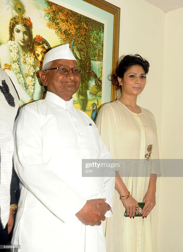 Indian Bollywood actress Tanishaa Mukerji (R) poses with Indian social activist Anna Hazare during the poster launch of upcoming Hindi biopic film ANNA Kisan Baburao Hazare' directed by Shashank Udapurkar, in Mumbai on June 27, 2016. / AFP / STR