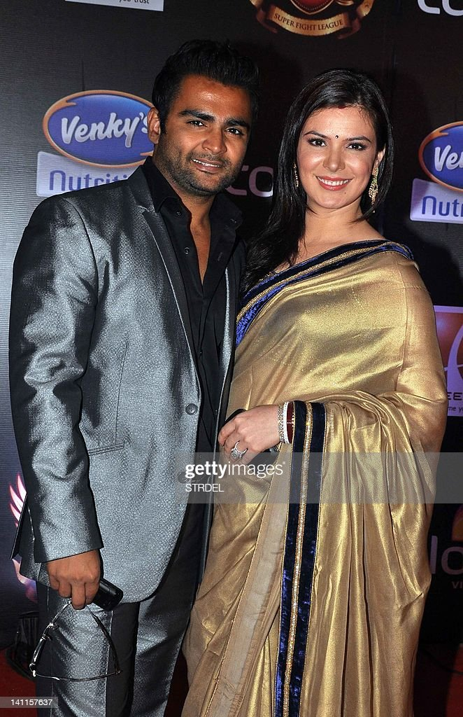 Indian Bollywood actress Urvashi Sharma (R) with husband Sachin Joshi pose as they arrive for the inaugural Super Fight League (SFL) in Mumbai on March 11, 2012. SFL is a mixed martial arts fighting league launched by Raj Kundra and Sanjay Dutt. AFP PHOTO/STR