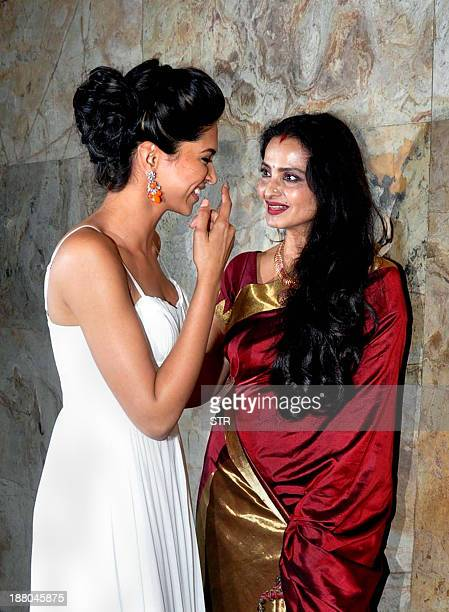 Indian Bollywood actresses Deepika Padukone and Rekha share a light moment during a special screening of Hindi film RaamLeela' produced and directed...