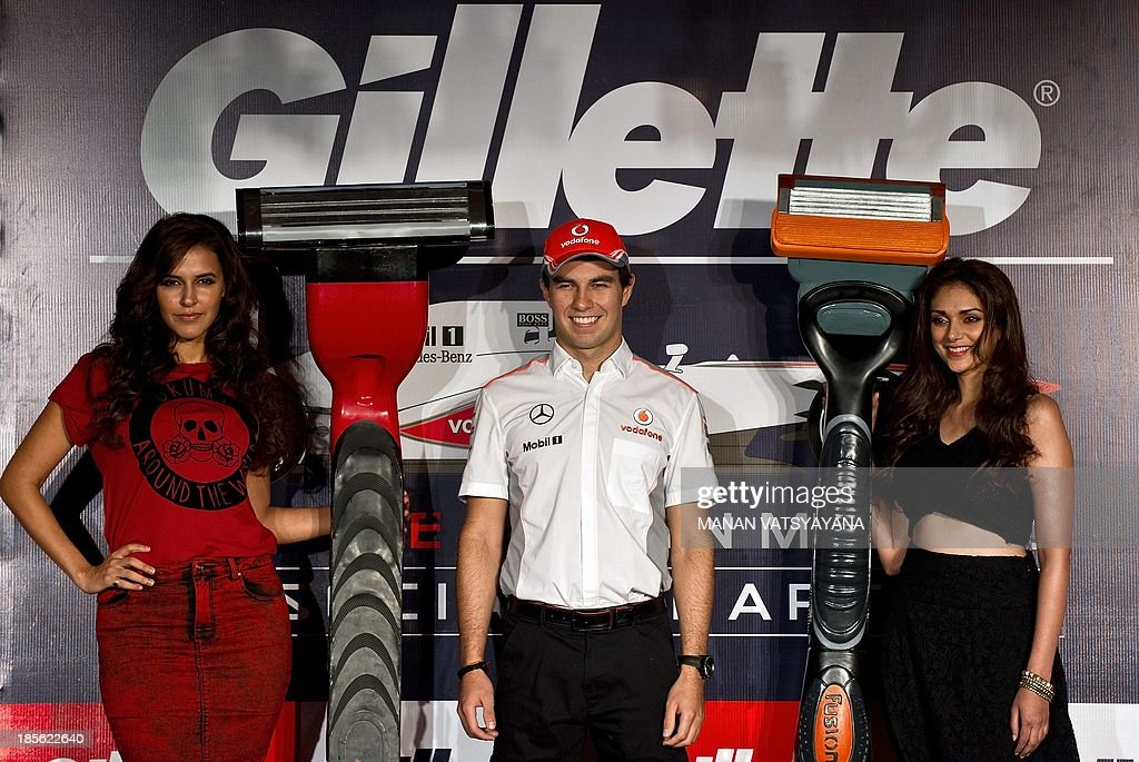 Indian Bollywood actresses Neha Dhupia (L) and Aditi Rao Hydari (R) with McLaren driver Sergio Perez Mendoza of Mexico (C) pose during a promotional event ahead of the Indian Grand Prix in New Delhi on October 23, 2013. The 2013 Indian Formula One Grand Prix takes place in Greater Noida on the outskirts of New Delhi on October 27.