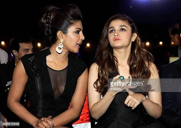 Indian Bollywood actresses Priyanka Chopra and Alia Bhatt speak as they attend the BIG STAR Entertainment Awards 2014 in Mumbai on December 18 2014...