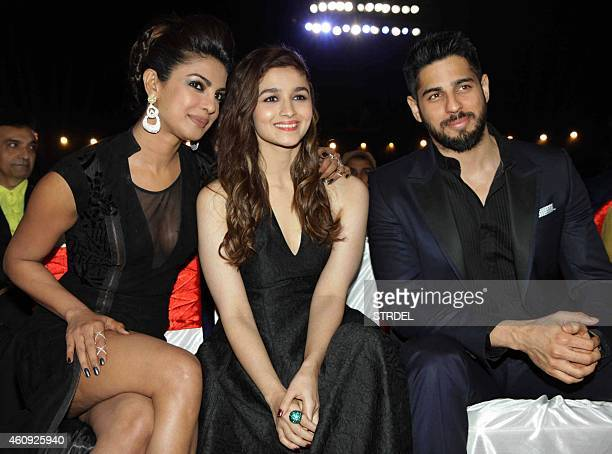 Indian Bollywood actresses Priyanka Chopra and Alia Bhatt speak to actor Siddharth Malhotra as they attend the BIG STAR Entertainment Awards 2014 in...