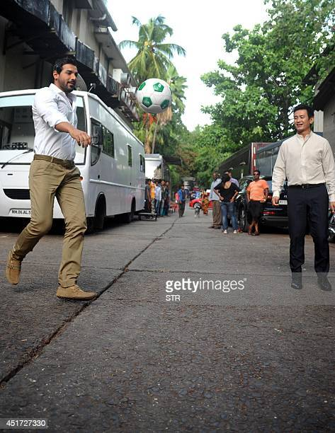 Indian Bollywood film actor John Abraham and Indian footballer Bhaichung Bhutia pose during the Indias Biggest Football Hangout using Google light...
