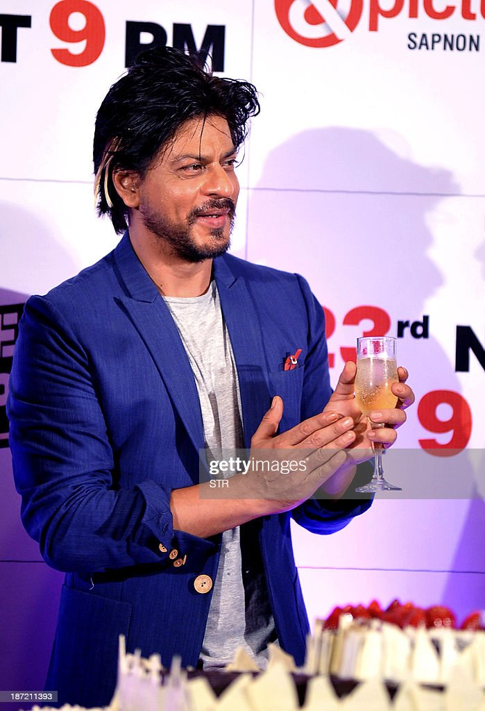 Indian Bollywood film actor Shahrukh Khan participates in the cake cutting during the success bash of Hindi film 'Chennai Express' directed by Rohit Shetty, in Mumbai on November 6, 2013.