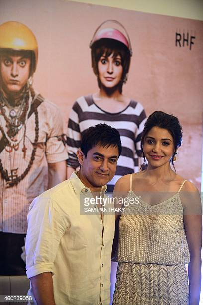 Indian Bollywood film actors Aamir Khan and Anuksha Sharma pose during the promotion of the forthcoming film 'PK' in Ahmedabad on December 10 2014...