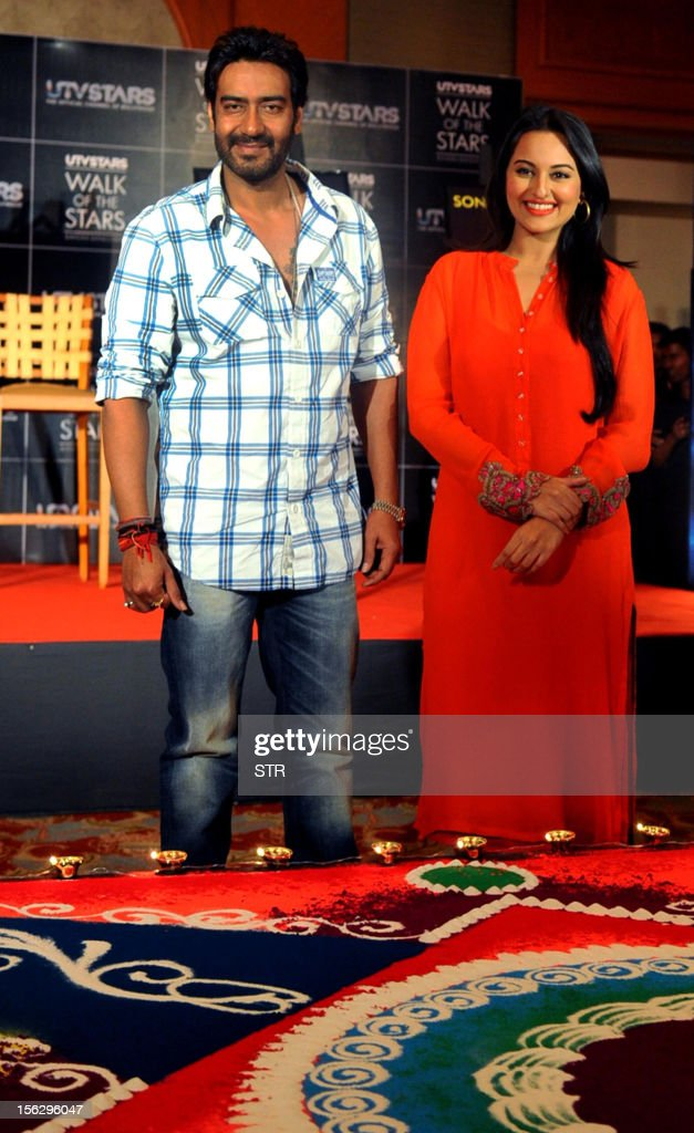 Indian Bollywood film actors Ajay Devgn (L) and Sonakshi Sinha pose during the unveiling of their respective tiles and the promotion of Hindi film 'Son of Sardar' during a celebration of Diwali with UTV Star in Mumbai on November 12, 2012.