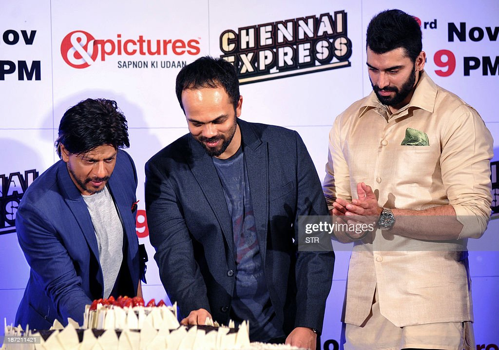 Indian Bollywood film actors Shahrukh Khan (L) and Nikitin Dheer (R) participate in the cake cutting during the success bash of Hindi film 'Chennai Express' directed by Rohit Shetty (C), in Mumbai on November 6, 2013.