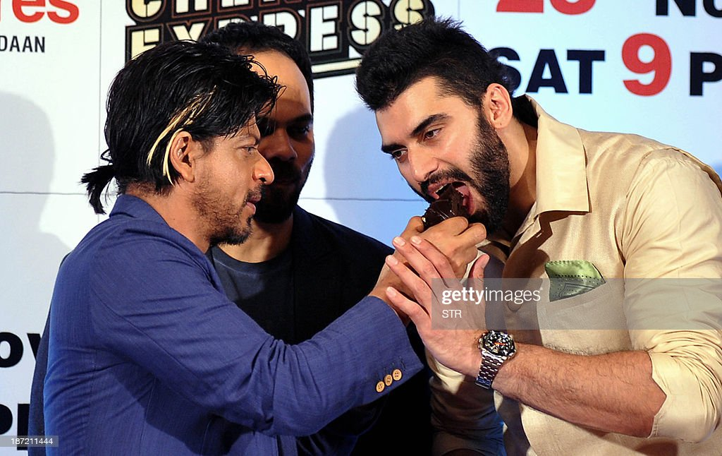 Indian Bollywood film actors Shahrukh Khan (L) and Nikitin Dheer (R) participate in the cake cutting during the success bash of Hindi film 'Chennai Express' directed by Rohit Shetty (C), in Mumbai on November 6, 2013. AFP PHOTO
