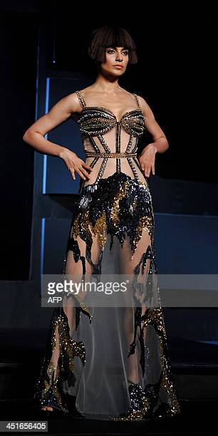 Indian Bollywood film actress Kangana Ranaut showcases a creation by designer Gavin Miguel during the 'Blenders Pride Fashion Tour 2013' in Mumbai on...
