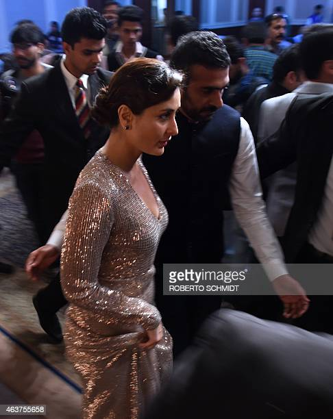 Indian Bollywood film actress Kareena Kapoor is escorted by a personal assistant at the end of an event during which she launched an ice cream bar at...