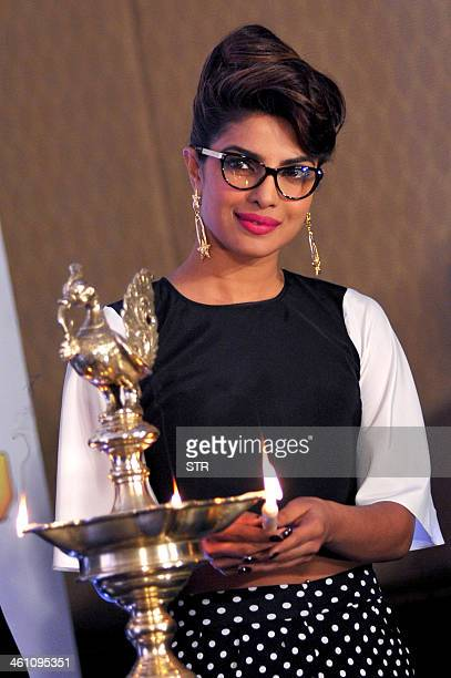 Indian Bollywood film actress Priyanka Chopra poses dueing the lighting of the lamp at the press conference of '59th Idea Filmfare Awards 2013' in...