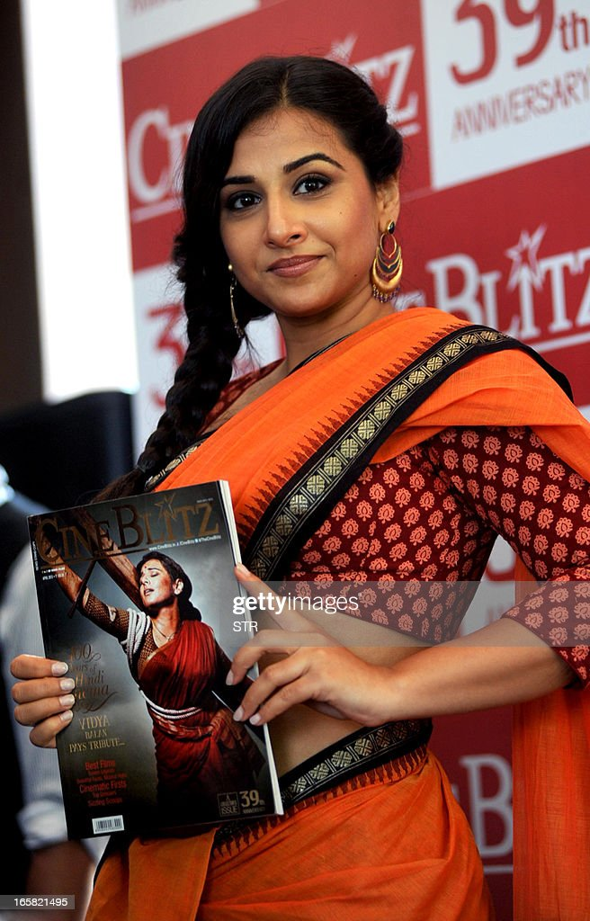Indian Bollywood film actress Vidya Balan holds a copy of the Cine Blitz magazine featuring herself as 'Mother India' during the unveiling of the 39th anniversary issue of Cine Blitz magazine 'Celebrating 100 Years of Hindi Cinema' in Mumbai on April 6, 2013. AFP PHOTO