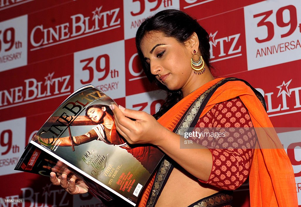 Indian Bollywood film actress Vidya Balan holds a copy of the Cine Blitz magazine featuring herself as 'Mother India' during the unveiling of the 39th anniversary issue of Cine Blitz magazine 'Celebrating 100 Years of Hindi Cinema' in Mumbai on April 6, 2013.
