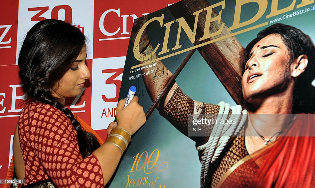 Indian Bollywood film actress Vidya Balan signs a poster of the Cine Blitz cover featuring herself as 'Mother India' during the unveiling of the 39th anniversary issue of Cine Blitz magazine 'Celebrating 100 Years of Hindi Cinema' in Mumbai on April 6, 2013.