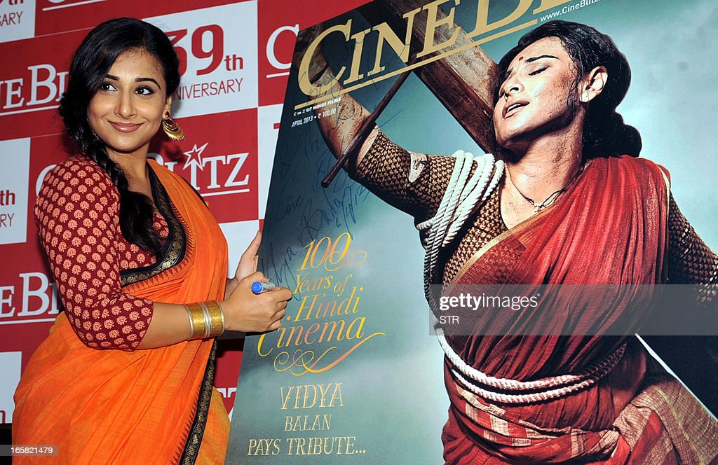 Indian Bollywood film actress Vidya Balan signs a poster of the Cine Blitz cover featuring herself as 'Mother India' during the unveiling of the 39th anniversary issue of Cine Blitz magazine 'Celebrating 100 Years of Hindi Cinema' in Mumbai on April 6, 2013. AFP PHOTO