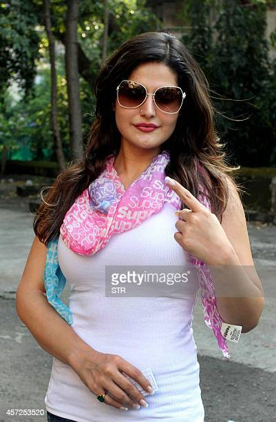 Indian Bollywood film actress Zarine Khan holds up her inkmarked finger after casting her vote in the Maharashtra Assembly Elections in Mumbai on...