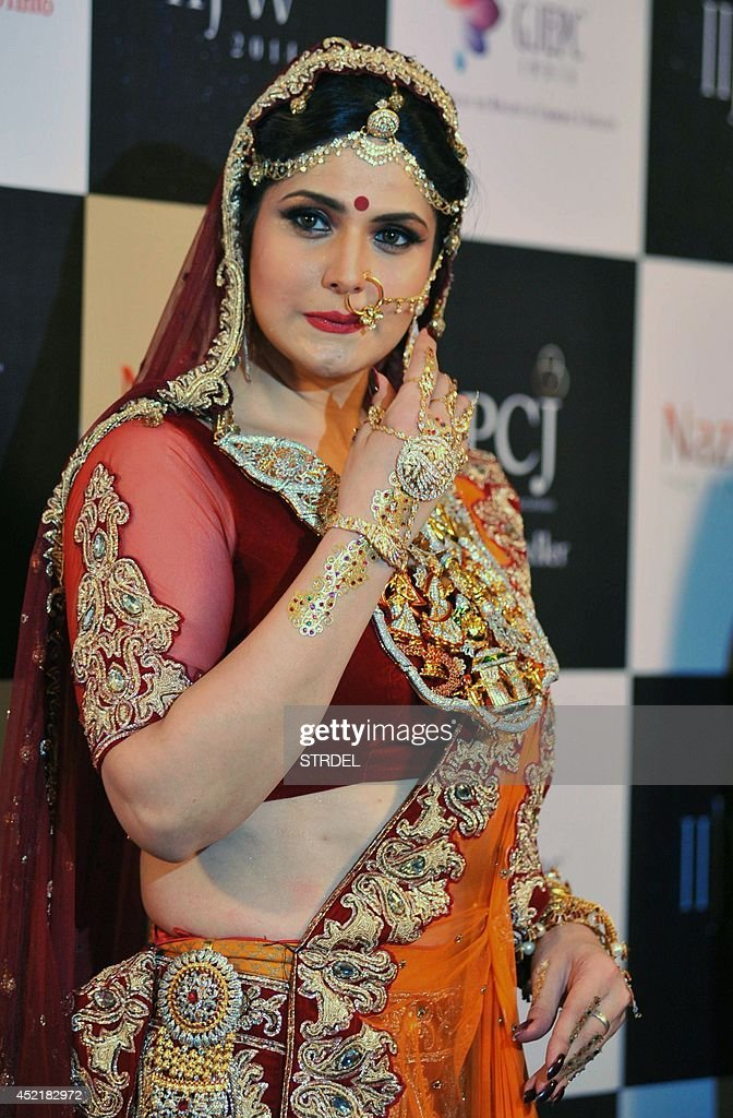 Indian Bollywood film actress <a gi-track='captionPersonalityLinkClicked' href=/galleries/search?phrase=Zarine+Khan&family=editorial&specificpeople=6381777 ng-click='$event.stopPropagation()'>Zarine Khan</a> presents a creation during the India International Jewellery Week 2014 (IIJW) in Mumbai on July 15, 2014.