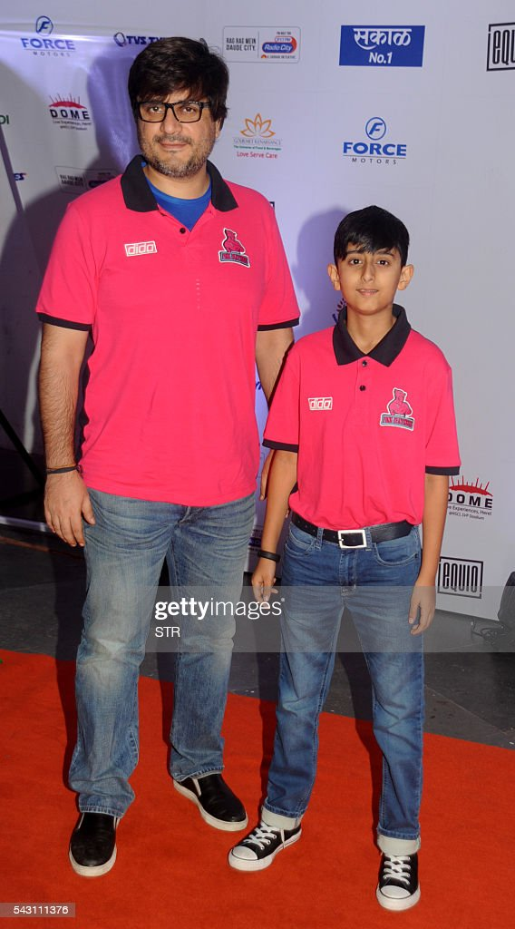 Indian Bollywood film director Goldie Behl poses for a photogrpah with his son during the opening ceremony for season four of the Pro-Kabaddi League in Mumbai on late June 25, 2016. / AFP / STR