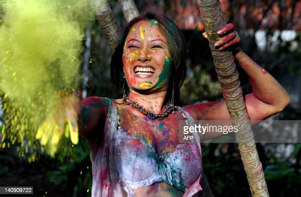 Indian Bollywood model and actress Pooja Basu throws powdered colours during the Indian Hindu festival of Holi in Mumbai on March 7 2012 'Holi' or...
