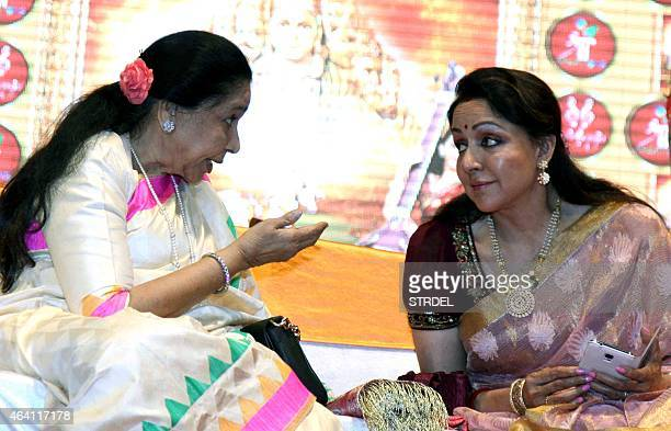 Indian Bollywood playback singer Asha Bhosle and actress Hema Malini speak during a devotional album and book launch of Veena Mundhra's Shri Hari...