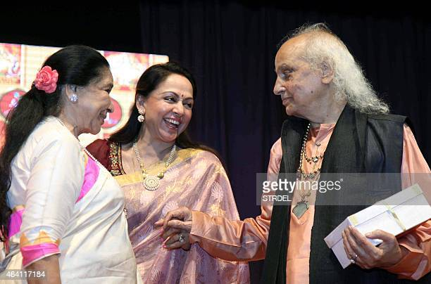 Indian Bollywood playback singer Asha Bhosle and actress Hema Malini speak with Indian classical vocalist Pandit Jasraj during a devotional album and...