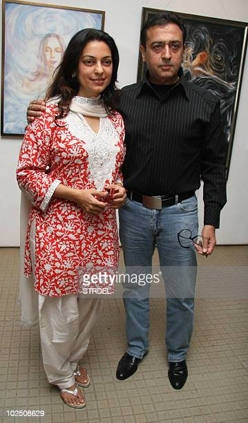 Indian Bollywood thespians Juhi Chawla and Gulshan Grover pose beside a painting at the opening of an exhibition at The Museum Art Gallery in Mumbai...
