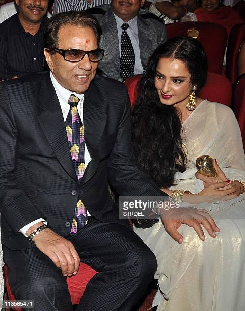 Indian Bollywood veteran actor Dharmendra sits with actress Rekha during the Dadasaheb Phalke Awards 2011 ceremony in Mumbai on May 3 2011 The...