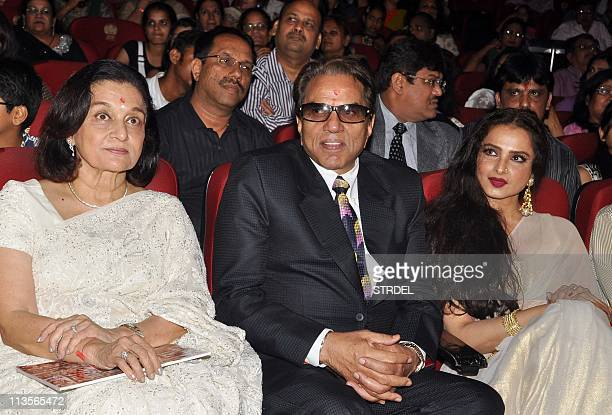 Indian Bollywood veteran actor Dharmendra sits with actresses Asha Parekh and Rekha during the Dadasaheb Phalke Awards 2011 ceremony in Mumbai on May...