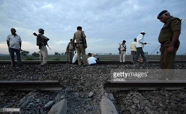 Indian bomb squad personnel and security officials survey damage to rails as they search railway tracks on the outskirts of Bodhgaya early August 3...