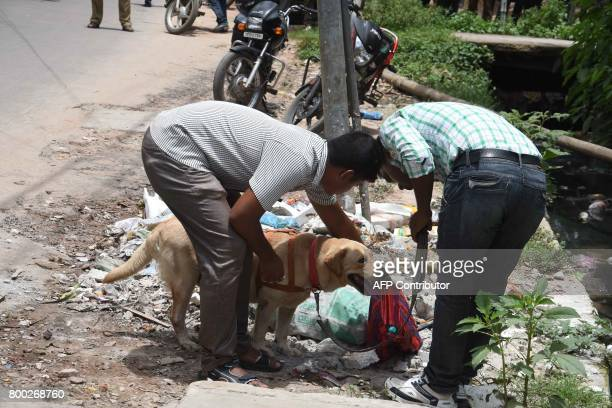 Indian bomb squad personnel inspect with a sniffer dog an unclaimed bag containing three crude bombs near a mosque in Agartala the capital of...
